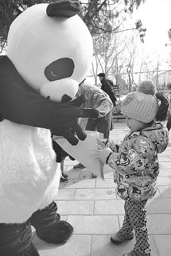 大熊猫馆前,卡通大熊猫向参加猜谜语活动的小朋友